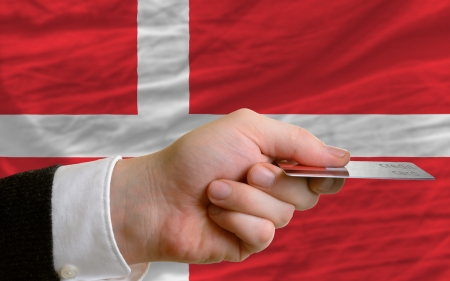 man stretching out credit card to buy goods in front of complete wavy national flag of denmark photo