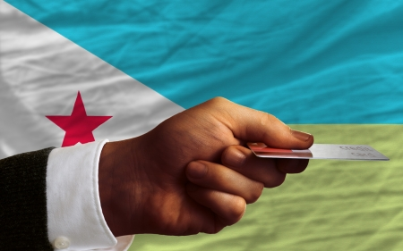 surplus: man stretching out credit card to buy goods in front of complete wavy national flag of djibouti
