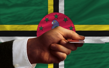 man stretching out credit card to buy goods in front of complete wavy national flag of dominica photo