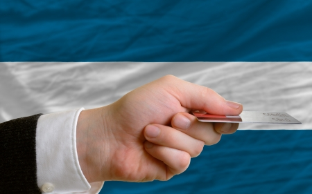 man stretching out credit card to buy goods in front of complete wavy national flag of el salvador photo