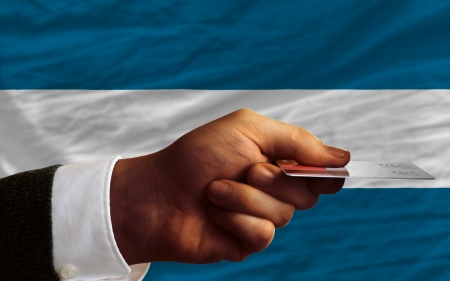 el salvadoran: man stretching out credit card to buy goods in front of complete wavy national flag of el salvador