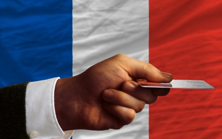 man stretching out credit card to buy goods in front of complete wavy national flag of france photo