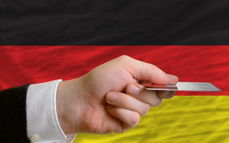man stretching out credit card to buy goods in front of complete wavy national flag of germany photo