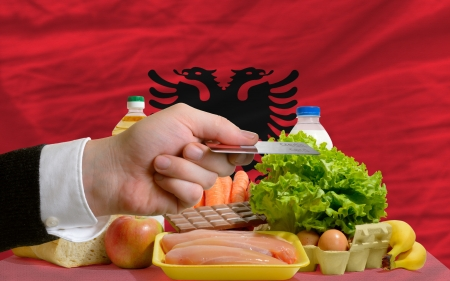 man stretching out credit card to buy food in front of complete wavy national flag of albania photo