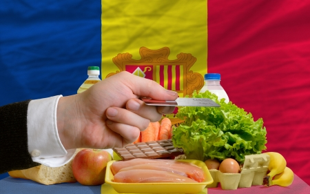 man stretching out credit card to buy food in front of complete wavy national flag of andorra Stock Photo - 14045351