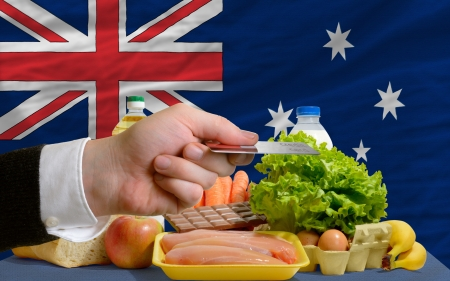 man stretching out credit card to buy food in front of complete wavy national flag of australia photo