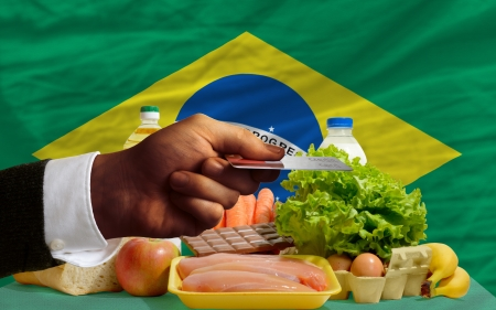 man stretching out credit card to buy food in front of complete wavy national flag of brazil photo