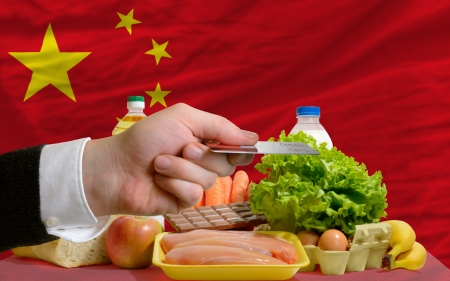 man stretching out credit card to buy food in front of complete wavy national flag of china photo