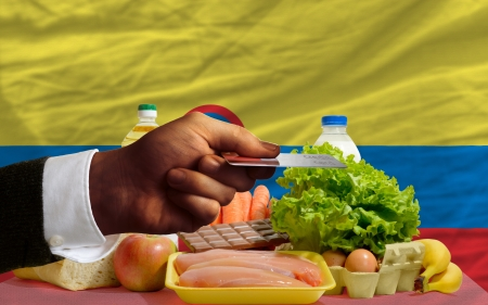 man stretching out credit card to buy food in front of complete wavy national flag of colombia photo