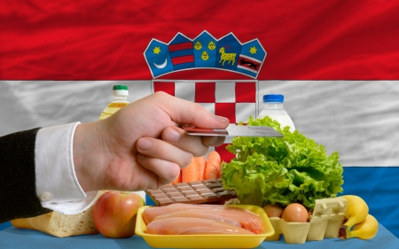 man stretching out credit card to buy food in front of complete wavy national flag of croatia photo