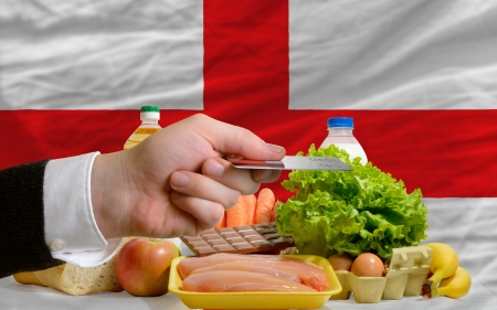 man stretching out credit card to buy food in front of complete wavy national flag of england photo