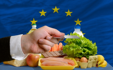 man stretching out credit card to buy food in front of complete wavy national flag of europe photo