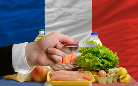 man stretching out credit card to buy food in front of complete wavy national flag of france Stock Photo - 14045277