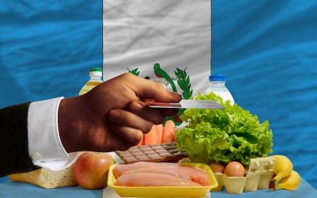 man stretching out credit card to buy food in front of complete wavy national flag of guatemala photo