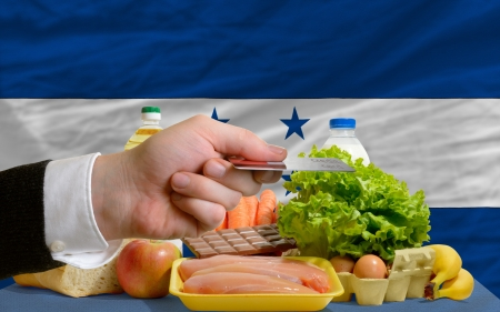 man stretching out credit card to buy food in front of complete wavy national flag of honduras photo