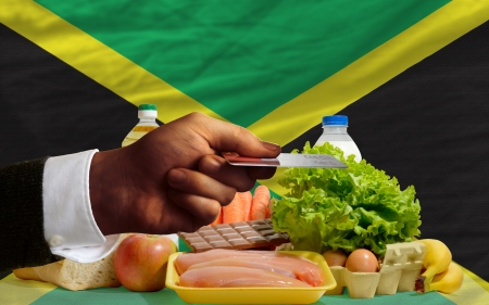 man stretching out credit card to buy food in front of complete wavy national flag of jamaica photo
