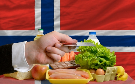 man stretching out credit card to buy food in front of complete wavy national flag of norway photo