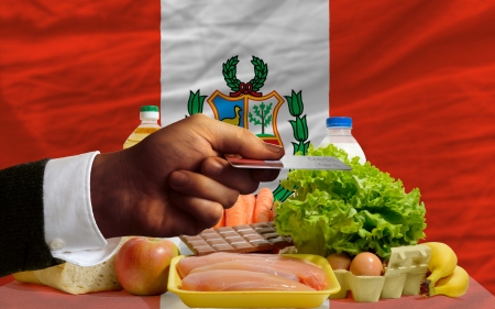 man stretching out credit card to buy food in front of complete wavy national flag of peru photo