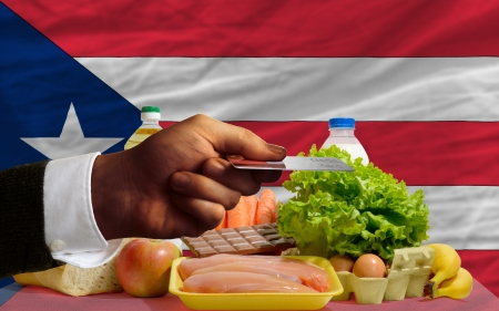 puertorico: man stretching out credit card to buy food in front of complete wavy national flag of puertorico