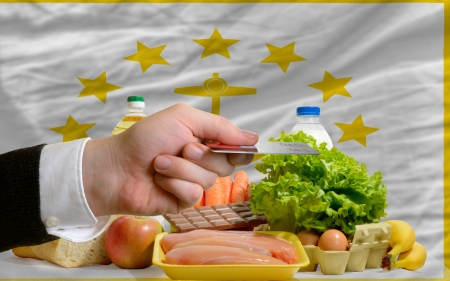 man stretching out credit card to buy food in front of complete wavy american state flag of rhode island photo