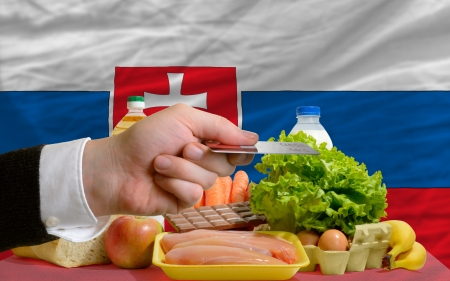 man stretching out credit card to buy food in front of complete wavy national flag of russia Stock Photo - 14045056