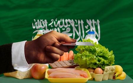 man stretching out credit card to buy food in front of complete wavy national flag of saudi arabia photo