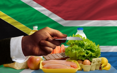 man stretching out credit card to buy food in front of complete wavy national flag of south africa photo