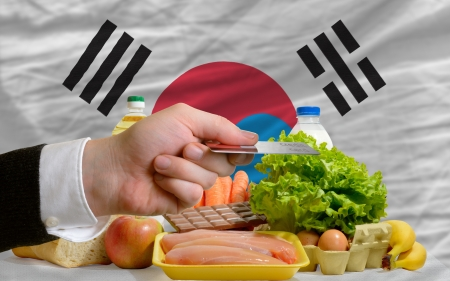 man stretching out credit card to buy food in front of complete wavy national flag of south korea photo