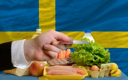 man stretching out credit card to buy food in front of complete wavy national flag of sweden photo