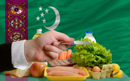 man stretching out credit card to buy food in front of complete wavy national flag of turkmenistan photo