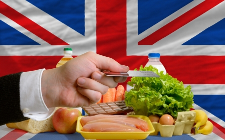 man stretching out credit card to buy food in front of complete wavy national flag of great britain photo
