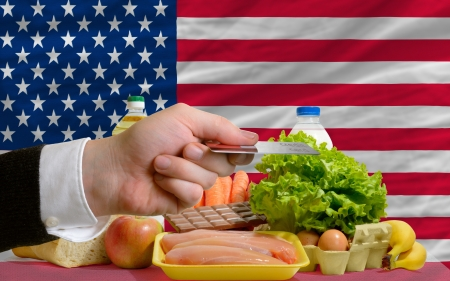 man stretching out credit card to buy food in front of complete wavy national flag of usa photo
