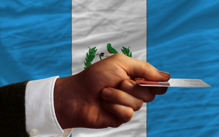 man stretching out credit card to buy goods in front of complete wavy national flag of guatemala photo