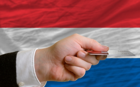 man stretching out credit card to buy goods in front of complete wavy national flag of holland photo