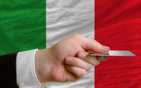 man stretching out credit card to buy goods in front of complete wavy national flag of italy photo