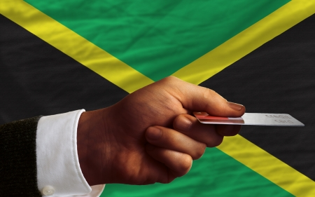 jamaican flag: man stretching out credit card to buy goods in front of complete wavy national flag of jamaica