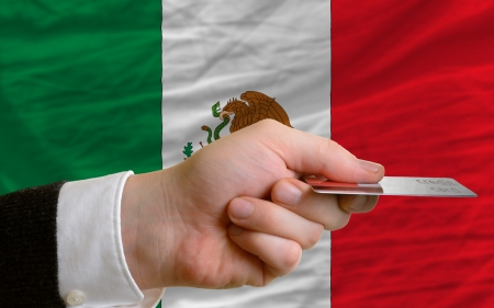 man stretching out credit card to buy goods in front of complete wavy national flag of mexico Stock Photo - 14045111