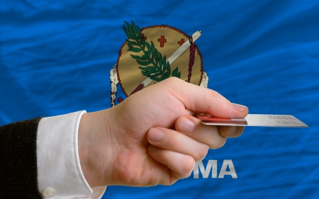 man stretching out credit card to buy goods in front of complete wavy national flag of american state of oklahoma photo