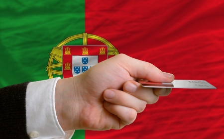 man stretching out credit card to buy goods in front of complete wavy national flag of portugal photo