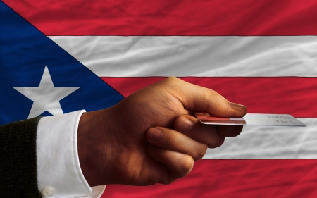 man stretching out credit card to buy goods in front of complete wavy national flag of puerto rico