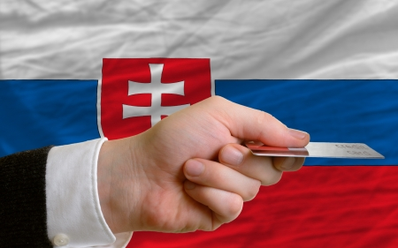 man stretching out credit card to buy goods in front of complete wavy national flag of slovakia photo