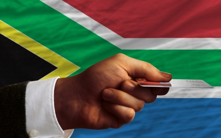 man stretching out credit card to buy goods in front of complete wavy national flag of south africa photo