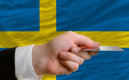 man stretching out credit card to buy goods in front of complete wavy national flag of sweden photo