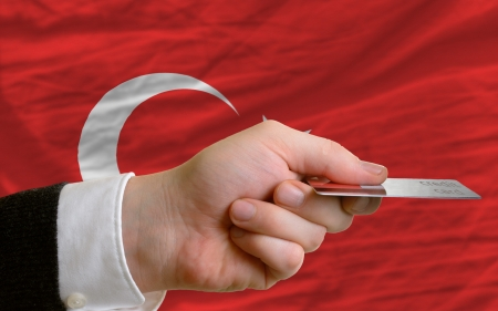 man stretching out credit card to buy goods in front of complete wavy national flag of turkey photo