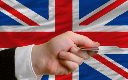 man stretching out credit card to buy goods in front of complete wavy national flag of great britain photo