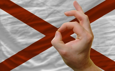 man showing excellence or ok gesture in front of complete wavy american state flag of alabamasymbolizing best quality, positivity and succes photo