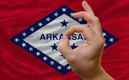 man showing excellence or ok gesture in front of complete wavy american state flag of arkansas symbolizing best quality, positivity and succes photo
