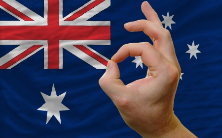 man showing excellence or ok gesture in front of complete wavy australia national flag of  symbolizing best quality, positivity and succes photo