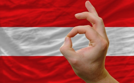 man showing excellence or ok gesture in front of complete wavy austria national flag of  symbolizing best quality, positivity and succes photo
