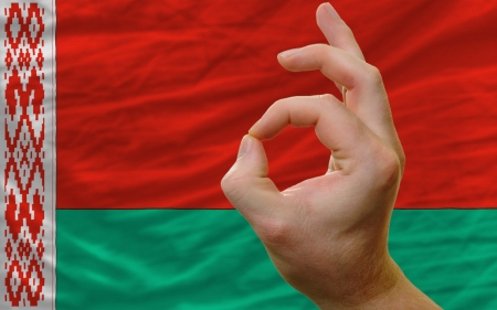 man showing excellence or ok gesture in front of complete wavy belarus national flag of  symbolizing best quality, positivity and succes photo